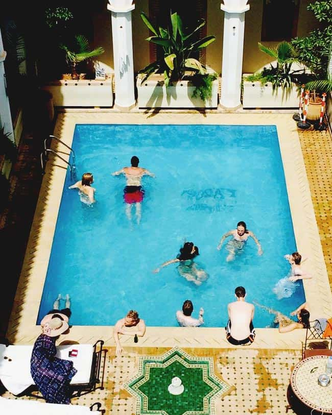 Backpacker sharing a swimming pool at Equity Point Marrakech